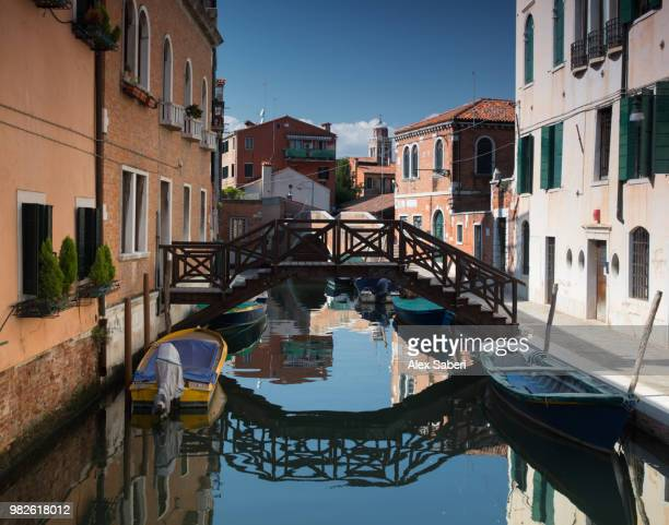 A colorful Venetian canal scene in the daylight hours.