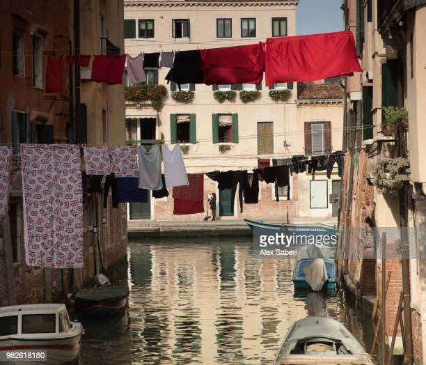 A colorful Venetian canal scene with clotheslines at sunset.