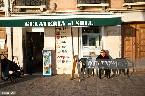 Venice, Italy: Senior Woman Sits Outside at Gelateria in Sunlight