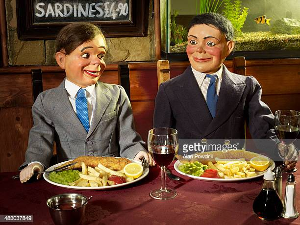 2 ventriloquist dolls in a restaurant - ventriloquist stock photos and pictures