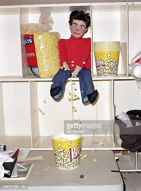 ventriloquist dummy sitting on shelf with popcorn - male likeness stock pictures, royalty-free photos & images