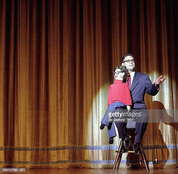 ventriloquist sitting on stage with dummy - ventriloquist stock photos and pictures