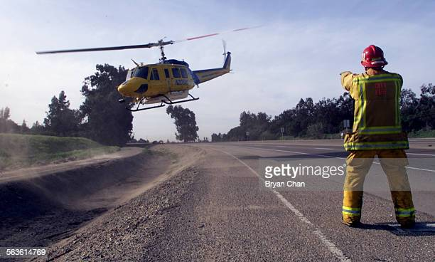 Ventura City firefighter Mike Fargo signals a rescue helicopter as it takes off carrying the pregnant driver of a car involved in a fatal crash on...