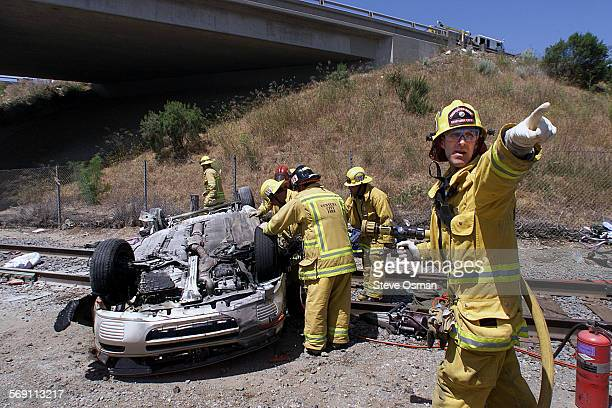 Ventura City firefighter/paramedic Matt Clapsaddle directs fellow firefighters while standing by with a fire hose next to a fatal accident in which a...