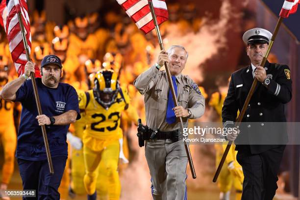 Ventura County Fire California Highway Patrol and Los Angeles Fire Department members carry flags onto the field before the start of the game between...