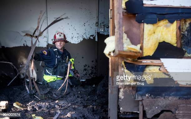 Ventura County fire captain Clay Cundiff searches in thigh deep mud in the bedroom of a home for a woman who was reported missing by friends and...
