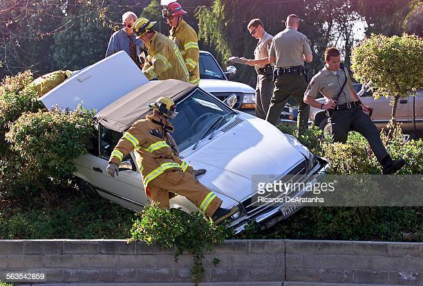 Ventura County Sheriff's deputies and fire fighters surrounding this Mercedes Bens down a landscaped area edging the parking lot of a strip mall on...