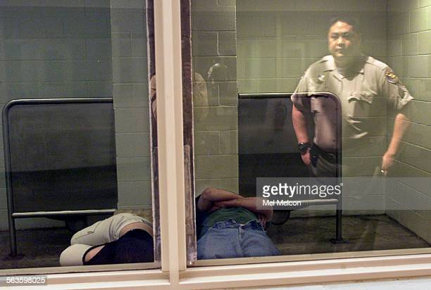 Ventura County Sheriff's senior deputy Ed Ilano is reflected in window as 2 arrestees lie down in their individual holding cells at the East County...