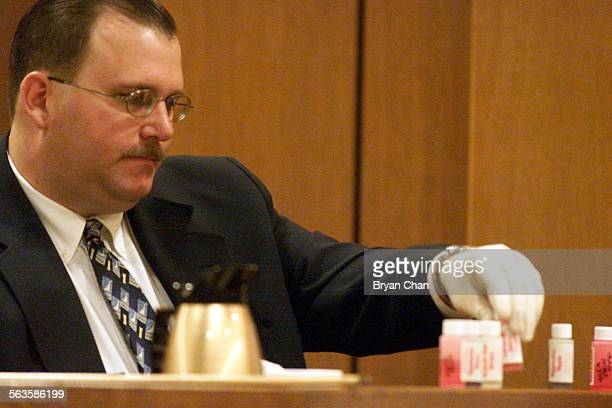 Ventura County Sheriff's Senior Deputy Scott Peterson looks at vials of chemicals collected in a search of Andrew Luster's home while on the witness...