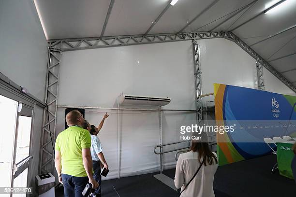 Venue operations staff look at a bullet hole inside the media centre at the Olympic Equestrian Centre after a bullet went through the wall of the...