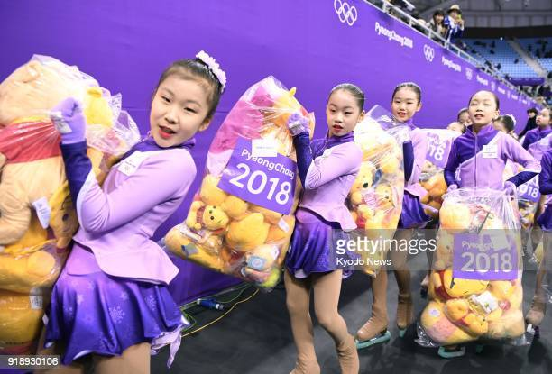 Venue staff members carry Winnie the Pooh dolls thrown into the rink after Japanese figure skater Yuzuru Hanyu's short program performance at the...