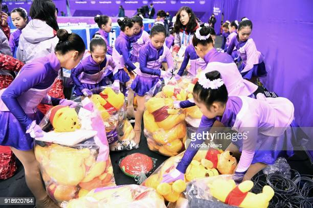 Venue staff members collect Winnie the Pooh dolls thrown into the rink after Japanese figure skater Yuzuru Hanyu's short program performance at the...