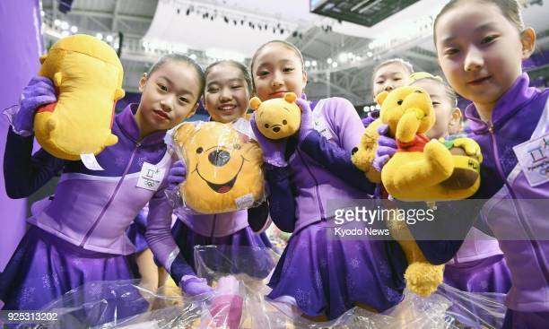 Venue staff members pose with Winnie the Pooh dolls thrown onto the rink after Japanese figure skater Yuzuru Hanyu's short program performance at the...