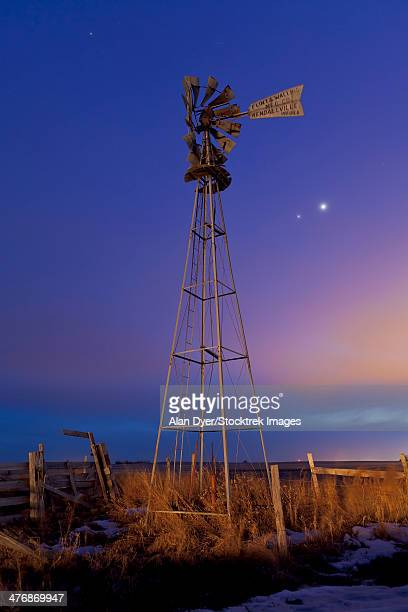 Venus and Jupiter are visible behind an old farm water pump windmill, Alberta, Canada.