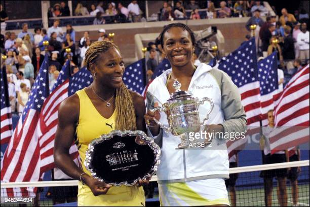 Venus and Serena Williams against a background of US flags with their US Open Trophies