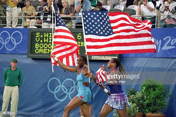 Venus and Serena Williams of the USA bring American flags onto the court to celebrate their win in the Women's Tennis Doubles event against Kristie...