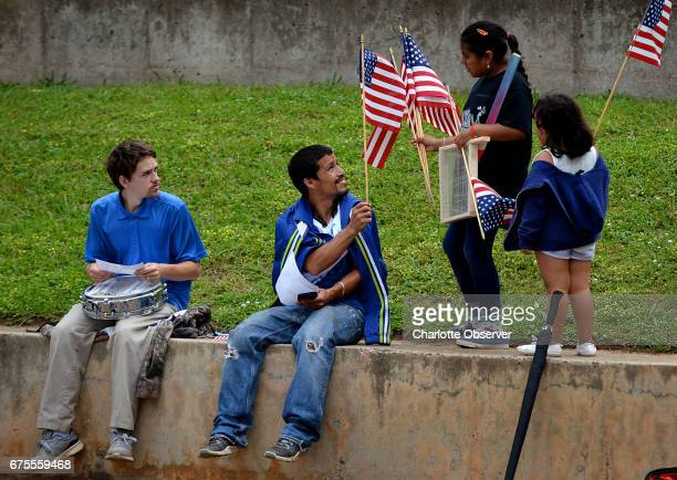Venus Betancourt second from right hands out American flags to people gathered at Marshall Park Monday May 1 2017 in Charlotte NC