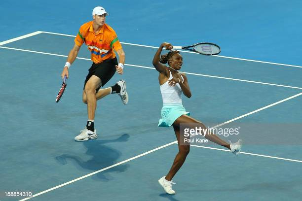 Venus Williams and John Isner of the USA return a shot in the mixed doubles match against Mathilde Johansson and Jo Wilfried Tsonga of France during...