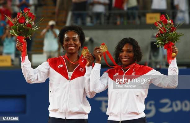 Venus Williams and Serena Williams of the United States celebrate the gold medal after defeating Virginia Ruano Pascual and Anabel Medina Garrigues...