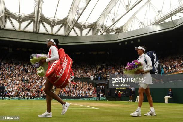 Venus Williams of The United States and Garbine Muguruza of Spain walk onto court prior to the Ladies Singles final on day twelve of the Wimbledon...
