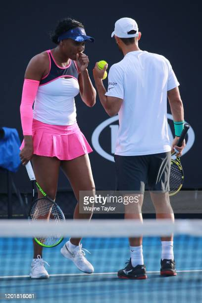 Venus Williams of the United States and Juan Sebastian Cabal of Colombia talk tactics during their Mixed Doubles first round match against Saisai...