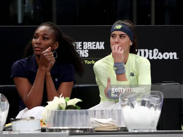 Venus Williams of the United States and Sorana Cirstea of Romania watch from the player bench during the Tie Break Tens at Madison Square Garden on...