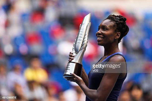 Venus Williams of the United States poses with her trophy after winning the women's singles final against Garbine Muguruza of Spain during day 7 of...