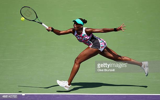 Venus Williams of the United States stretches to play a forehand against Caroline Wozniacki of Denmark in their fourth round match during the Miami...