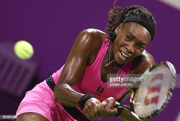 Venus Williams of the US returns the ball to Serbia's Jelena Jankovic during their WTA Championships semi-final tennis match at the Khalifa...