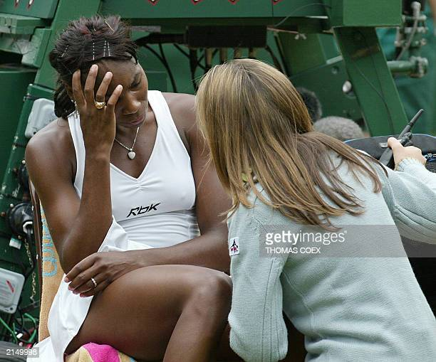 Venus Williams of the US speaks with the court doctor about an injury during her Ladies' Final match against Serena Williams of the US during their...