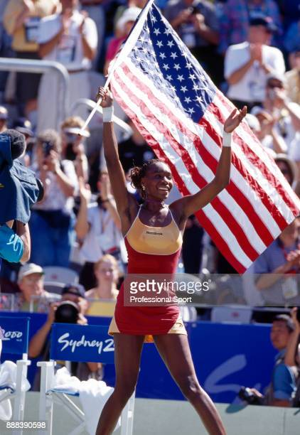 Venus Williams of the USA celebrates with the flag after defeating Elena Dementieva of Russia in the Women's Singles Gold Medal Match in the tennis...