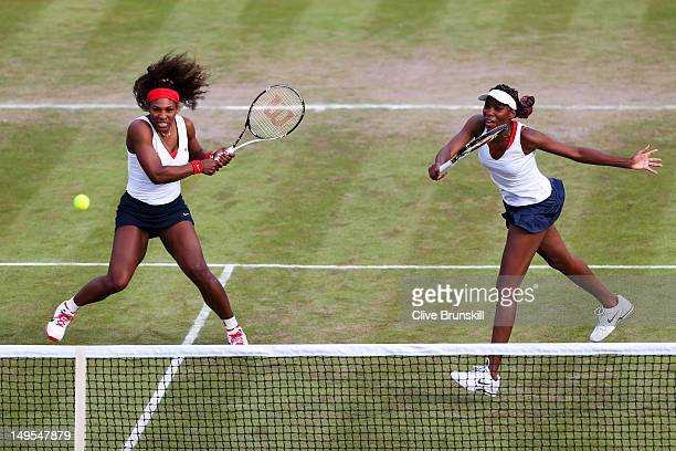 Venus Williams of United States hits a forehand next to her partner Serena Williams of the United States during their Women's Doubles Tennis match...