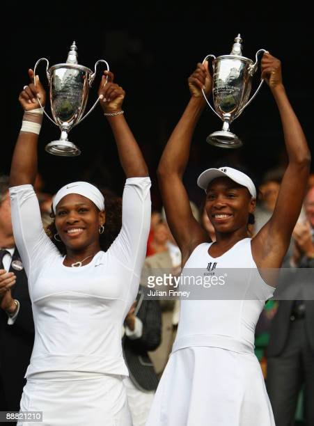 Venus Williams of USA and Serena Williams of USA celebrate victory with their trophies after the women's doubles final match against Samantha Stosur...