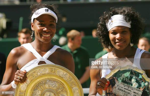 US Venus williams poses holding her trophy with her sister Serena after winning the final tennis match of the 2008 Wimbledon championships at The All...
