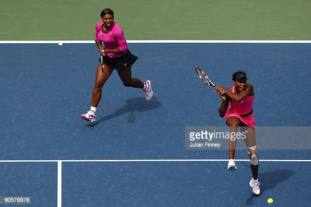 Venus Williams returns a shot while playing with Serena Williams during the semifinal doubles match against Alisa Kleybanova of Russia and Ekaterina...