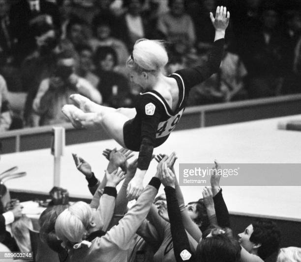 Vera Caslavska of Czechoslovakia is tossed into the air by her fellow gymnasts after judges awarded her 990 of a possible ten pints in the uneven...