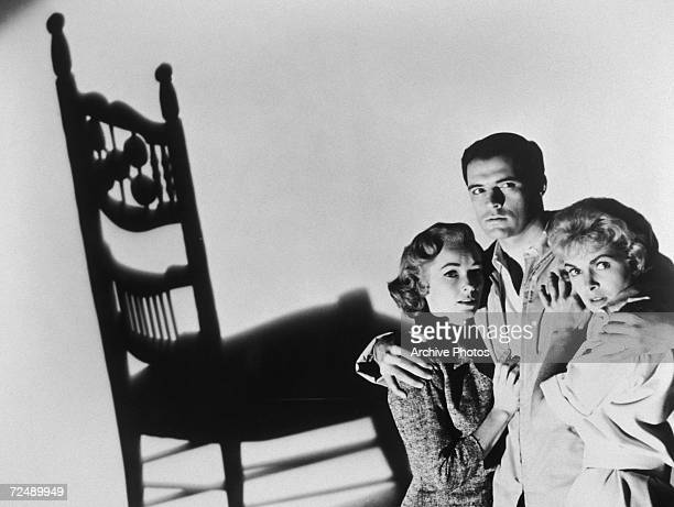 Vera Miles John Gavin and Janet Leigh cower beneath the shadow of a rocking chair in a promotional shot for the Alfred Hitchcock horror film 'Psycho'...