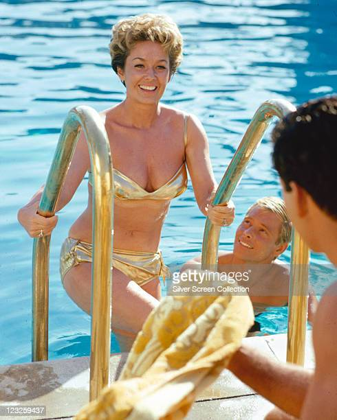 Vera Miles US actress smiling as she emerges from a swimming pool in a gold bikini with a male swimmer in the pool and another man handing Miles a...