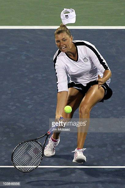 Vera Zvonareva of Russia loses her hat while returning a shot against Alexandra Dulgheru of Romania during day six of the 2010 US Open at the USTA...