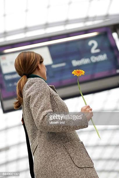 Verabredung Junge Frau wartet auf dem Bahnsteig mit einer Blume in der Hand