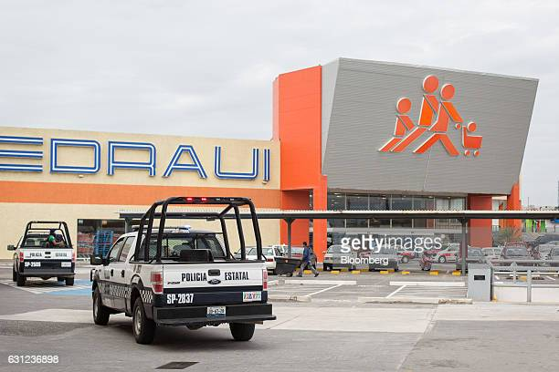 Veracruz state police vehicles patrol the parking lot of a Chedraui SA store following looting in Veracruz City Mexico on Sunday Jan 8 2017 Mexico's...
