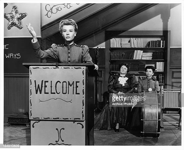 VeraEllen stands at a podium in front of Marjorie Main and Alice Pearce in a scene from the film 'The Belle Of New York' 1952