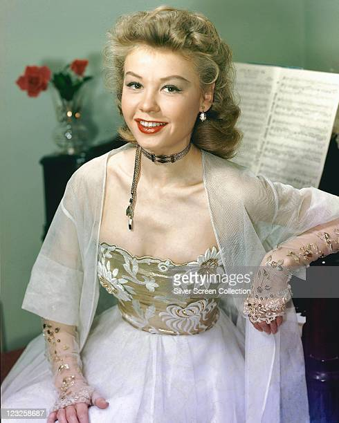 VeraEllen US actress and dancer wearing a lace coat over a dress with a gold bodice with a floral design and a silver choker posing with a piano and...