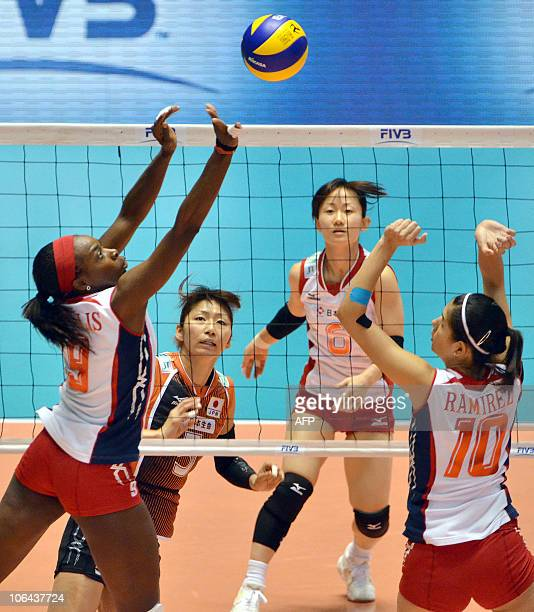 Verania Willis of Costa Rica sets the ball for team mate Paola Ramirez Vargas against Japan during their first round match of the women's volleyball...