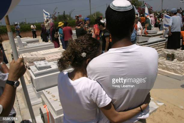 Vered Hazani hugs her husband Sahar as they stand next to the grave of her father Hanoh Sharabbi August 14 2005 in Neve Dkalim Gaza Strip The...