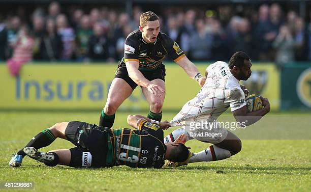 Vereniki Goneva of Leicester is tackled by George Pisi and George North during the Aviva Premiership match between Northampton Saints and Leicester...