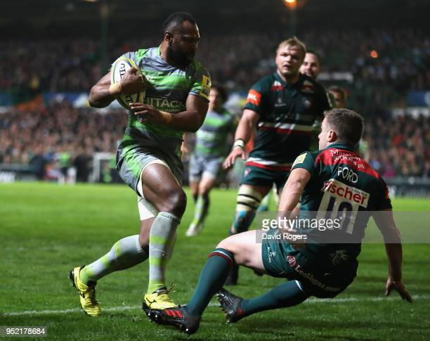Vereniki Goneva of Newcastle Falcons goes past George Ford to score his second try during the Aviva Premiership match between Leicester Tigers and...
