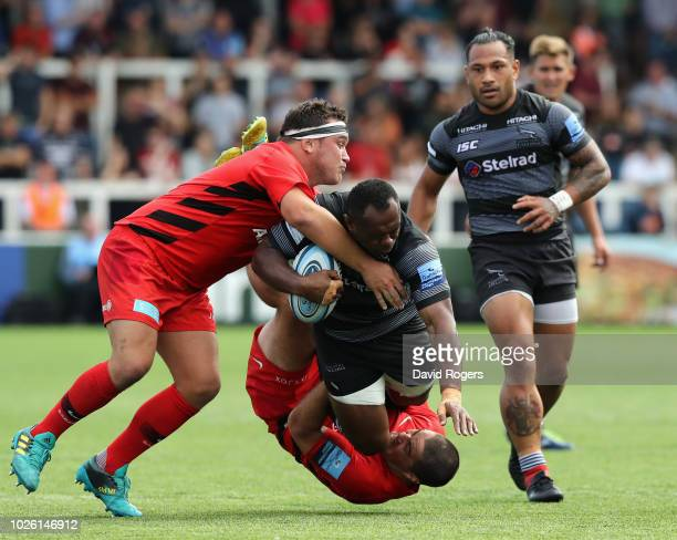 Vereniki Goneva of Newcastle is tackled by Jamie George and Brad Barritt during the Gallagher Premiership Rugby match between Newcastle Falcons and...