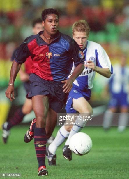 Verfolgt vom Hertha-Mittelfeldspieler Andreas Neuendorf , führt Barcelonas niederländischer Stürmer Patrick Kluivert den Ball am 6.8.1999 im Berliner...