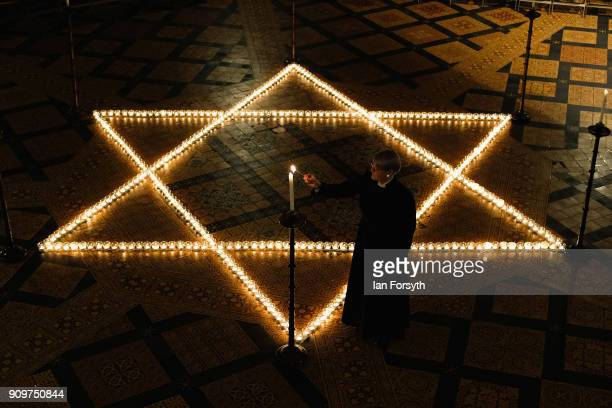 Verger Jessica Cook lights the six hundred candles set out on the floor in the form of the Star of David during a special event to commemorate...